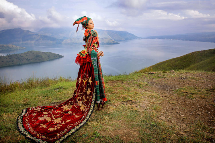 Woman wearing traditional clothing while standing on mountain against lake