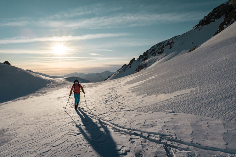 Man skitouring on a glacier with a sunrise background