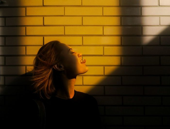 Side view of young woman sticking out tongue against wall during sunny day