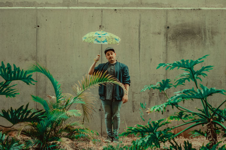 Portrait of man holding umbrella standing by wall amidst plants