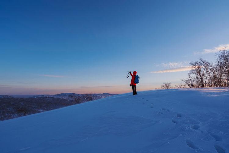 Man on snow field against blue sky