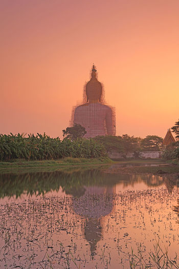 Beautiful view of big golden buddha at Wat Muang in during sunrise, Ang Thong province, Thailand Reflection Sky Built Structure Architecture Building Exterior Sunset Water Nature No People Lake Tree Plant Travel Destinations Building Outdoors Waterfront Beauty In Nature Scenics - Nature Travel Luxury Architecture River Temple Temple - Building Temple Architecture Religion Religion Architecture Orange Sky Ang Thong Thailand Buddhism Buddhism Temple