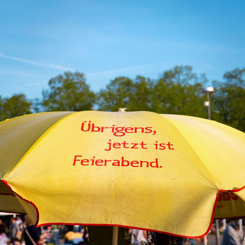 German Blue Sky Communication Day End Of Working Day Focus On Foreground Incidental People Leisure Time Message Nature Non-western Script Outdoors Parasol Plant Protection Real People Script Sign Sky Text Tree Umbrella Western Script Yellow Yellow Color #FREIHEITBERLIN
