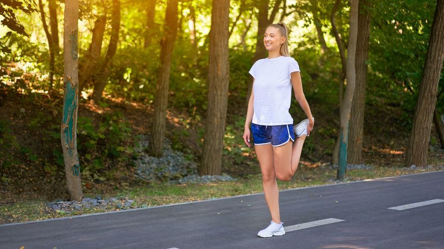 Full length portrait of young woman running on road