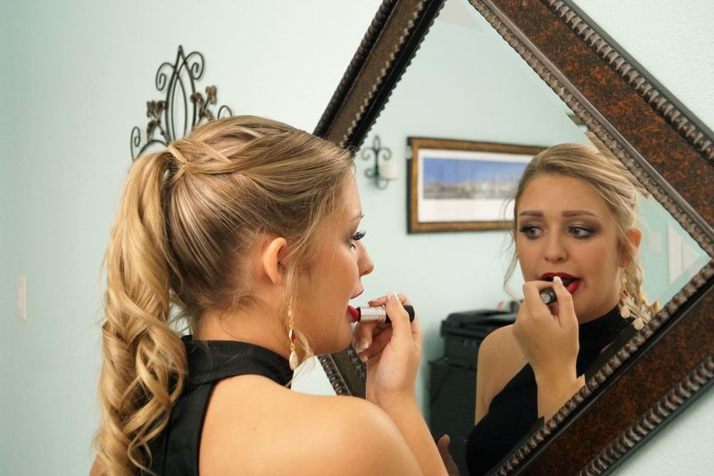 Young woman looking in mirror while applying lipstick at home