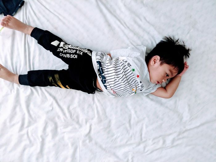 Directly above shot of boy lying on bed