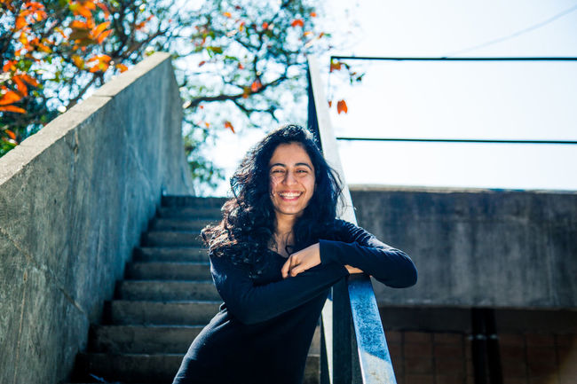 A young girl smiling & feeling happy on stairs. Portrait Beautiful Woman Students Student Life Girl Smiling Girl Laughing Young Girl In Stair Young Girl On Bridge Girl In College Curly Hair Girls <3