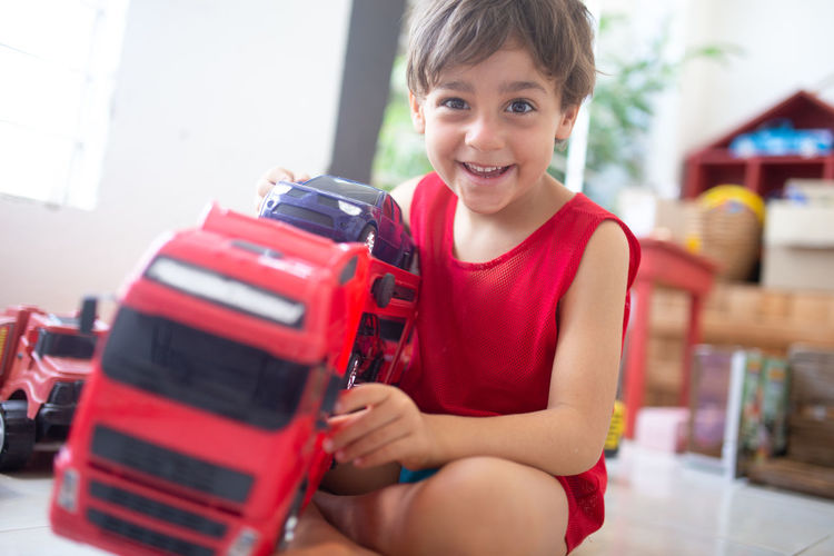 Portrait of boy playing with toy car while sitting on floor