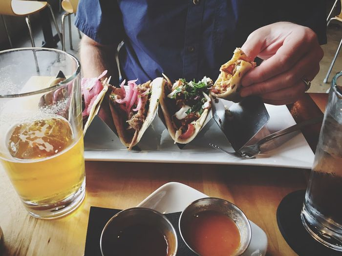 Midsection of man having tacos and beer at table in restaurant