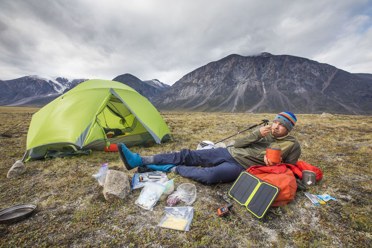 People sitting in tent on mountain against sky