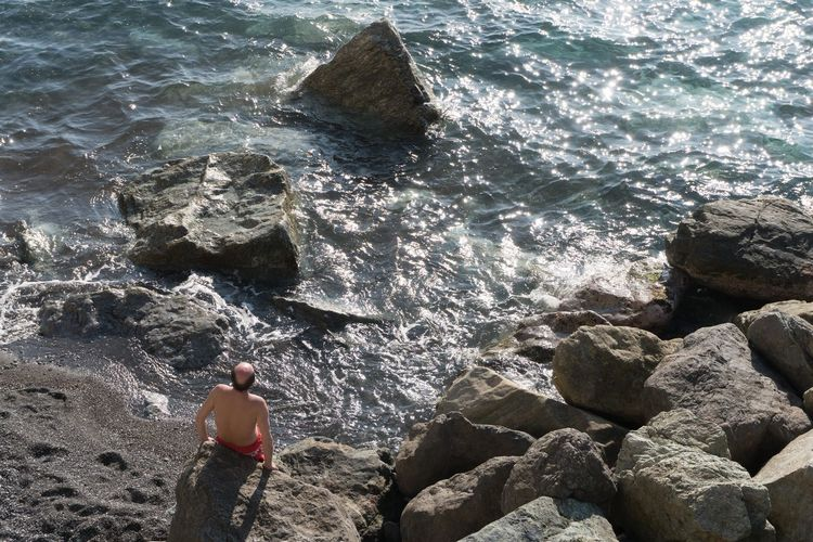 Rear view of shirtless man on rocks at beach