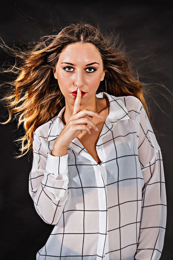 Portrait of beautiful woman with finger on lips against black background