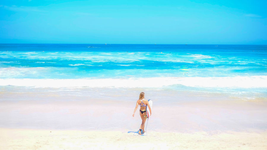 Rear view of bikini woman with surfboard walking at beach