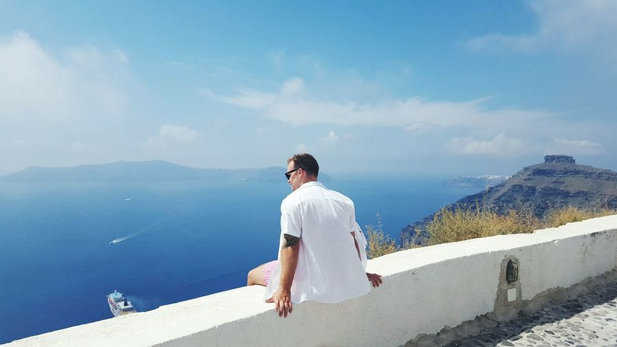 Man sitting on wall at beach against sky
