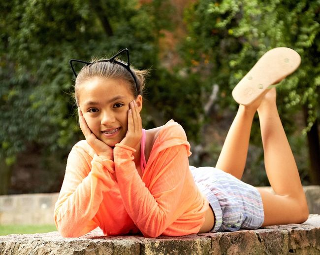 Portrait of smiling girl lying on retaining wall