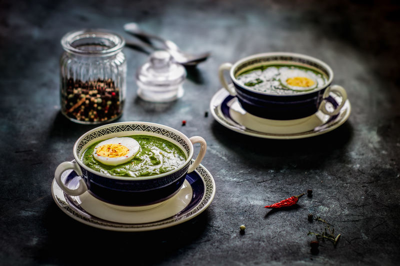 High angle view of spinach soup with egg with spice served on table