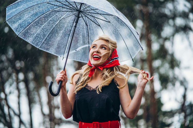 Woman holding umbrella standing during rainy season