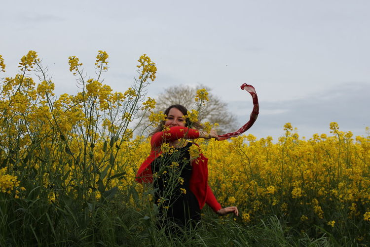 Portrait of cheerful young woman waving scarf while standing amidst yellow flowers blooming on field