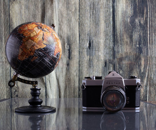 Old Pentax World Traveler Photography Themes Wood - Material Table Camera - Photographic Equipment Still Life Retro Styled Technology Indoors  No People Antique Photographic Equipment Old Close-up Wall - Building Feature Vintage Equipment Analog Globe - Man Made Object Photographing