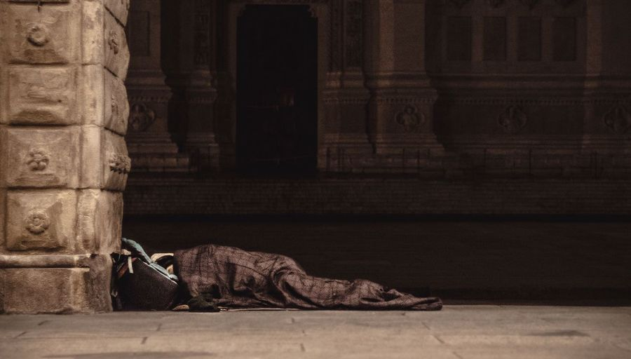 Refugee sleeping in building corridor on sunny day