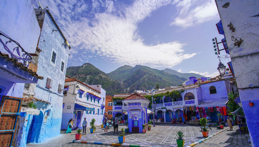"""""""The Blue City"""" We travelled from Sevilla to Tarifa, then took a ferry to Tangier, then a taxi to Chefchaouen, Morocco. EyeEmNewHere a new beginning Chefchaouen Morocco Beauty Blue City Blue Medina Building Exterior Architecture Mountain Cloud - Sky Real People Nature Group Of People Mountain Range Street Residential District Adult Outdoors Women Built Structure Building Sky Incidental People City Day People Digital Nomad"""