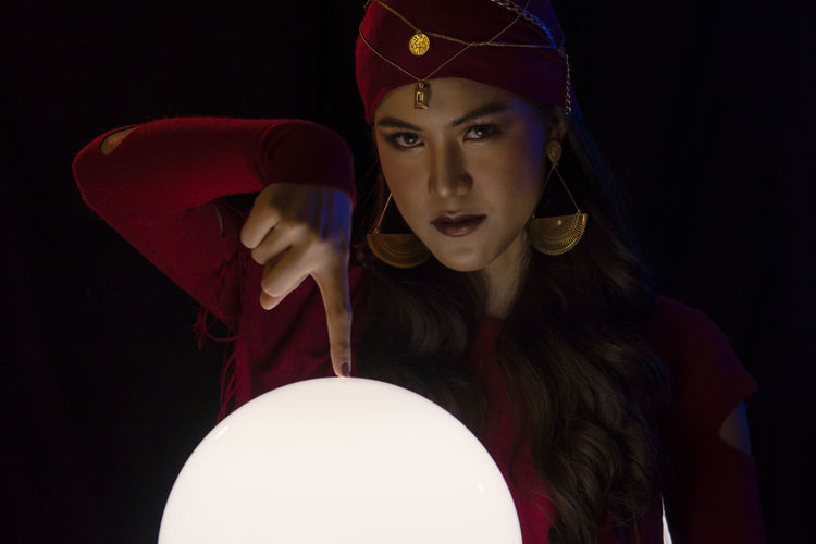 Portrait of female fortune teller pointing at sphere against black background