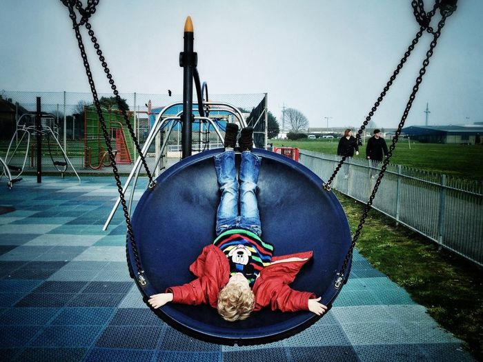 Upside down image of girl relaxing on footpath at park