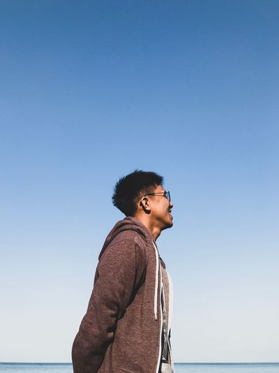 Low angle view of young man standing at beach against blue sky