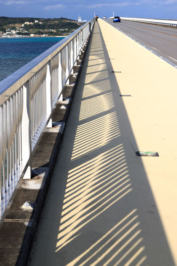 Shadow patterns from a bridge railing Architecture Bridge Built Structure Day Diminishing Perspective Direction Footpath High Angle View Long Nature No People Outdoors Pier Railing Shadow Sky Sunlight The Way Forward Water Wood - Material
