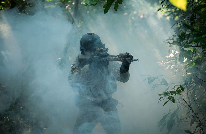Fully Equipped Soldiers Wearing Camouflage Uniform Attacking Enemy, Airsoft military game player in camouflage uniform Holding Water Nature One Person Three Quarter Length Smoke - Physical Structure Tree Day Real People Clothing Men Weapon Plant Outdoors Waist Up Males  Standing Musical Instrument