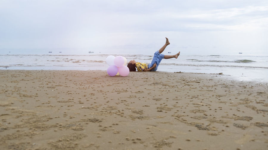 Asian young girl enjoy time playing balloone at the beach.