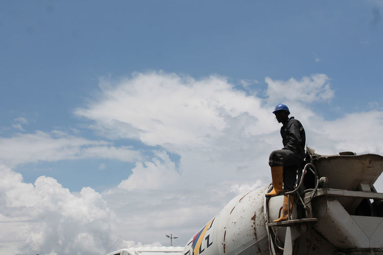 Low Angle View Of Construction Worker Standing On Cement Truck Against Sky