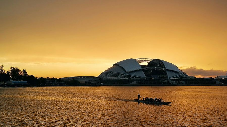 Silhouette boat sailing in river in front of singapore sports hub against orange sky during sunset