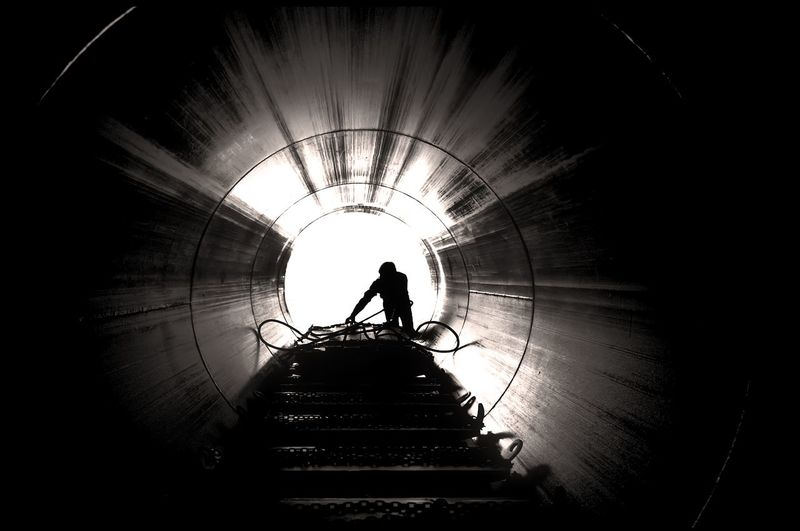 Worker at lumber treatment facility Action Built Structure Day Industry Silhouette Standing Tunnel Worker