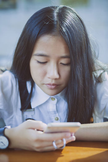 asian teenager reading message in smartphone Teenager Teen Reading Read Message Phone Smartphone Mobilephone Cellphone ASIA Asian  Girl Girls Thai Education School Student Studying Study Learning Face Headshot Body Part
