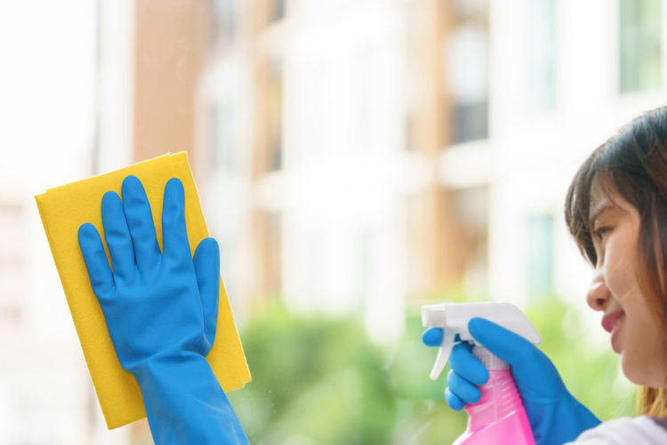 Woman Wearing Gloves While Cleaning Glass Window