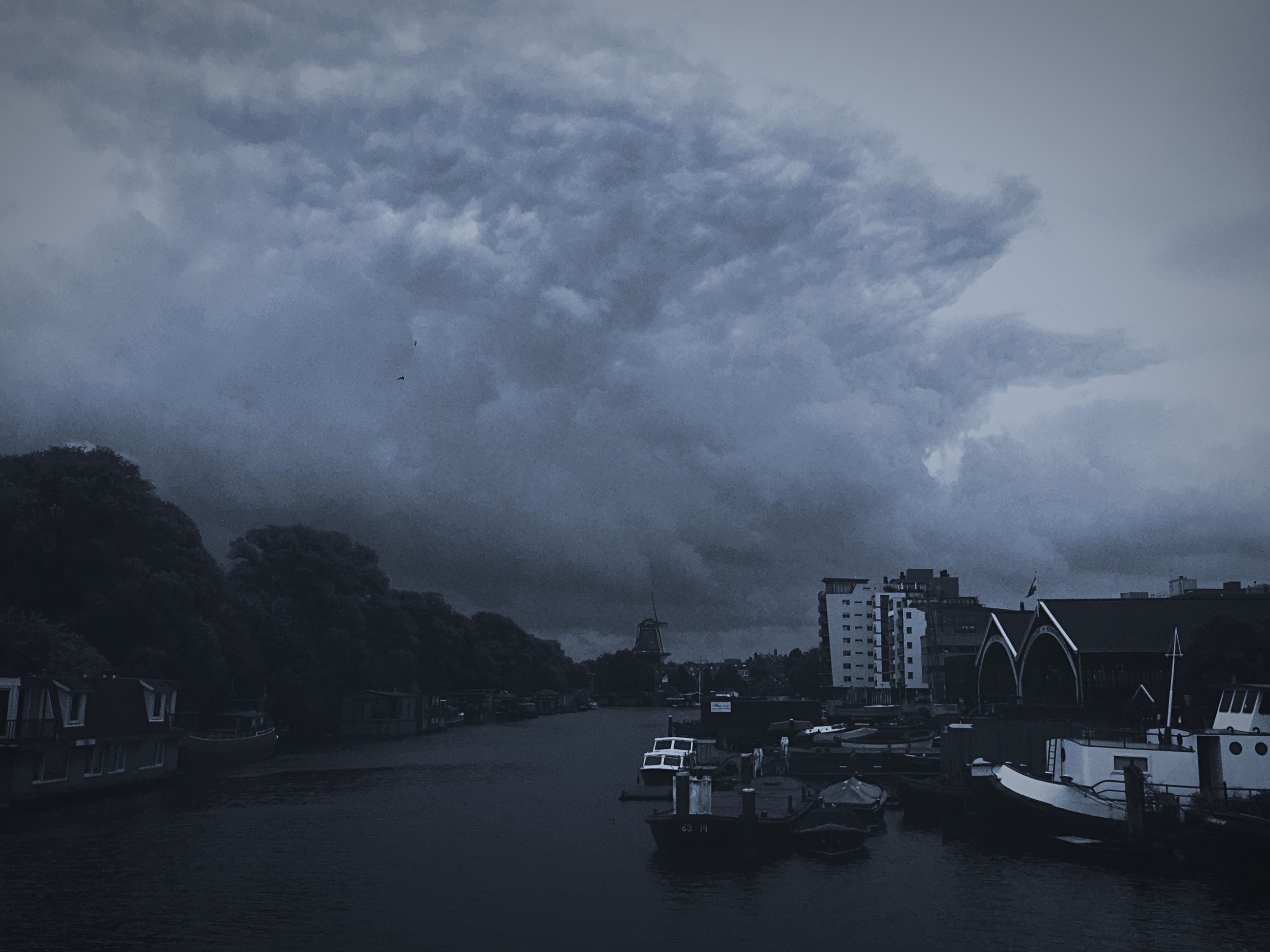 water, building exterior, sky, transportation, waterfront, architecture, nautical vessel, built structure, cloud - sky, mode of transport, cloudy, river, city, weather, boat, overcast, storm cloud, moored, dusk, nature