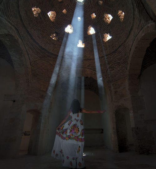 Rear View Of Woman Standing By Sunlight Streaming Through Ceiling Holes