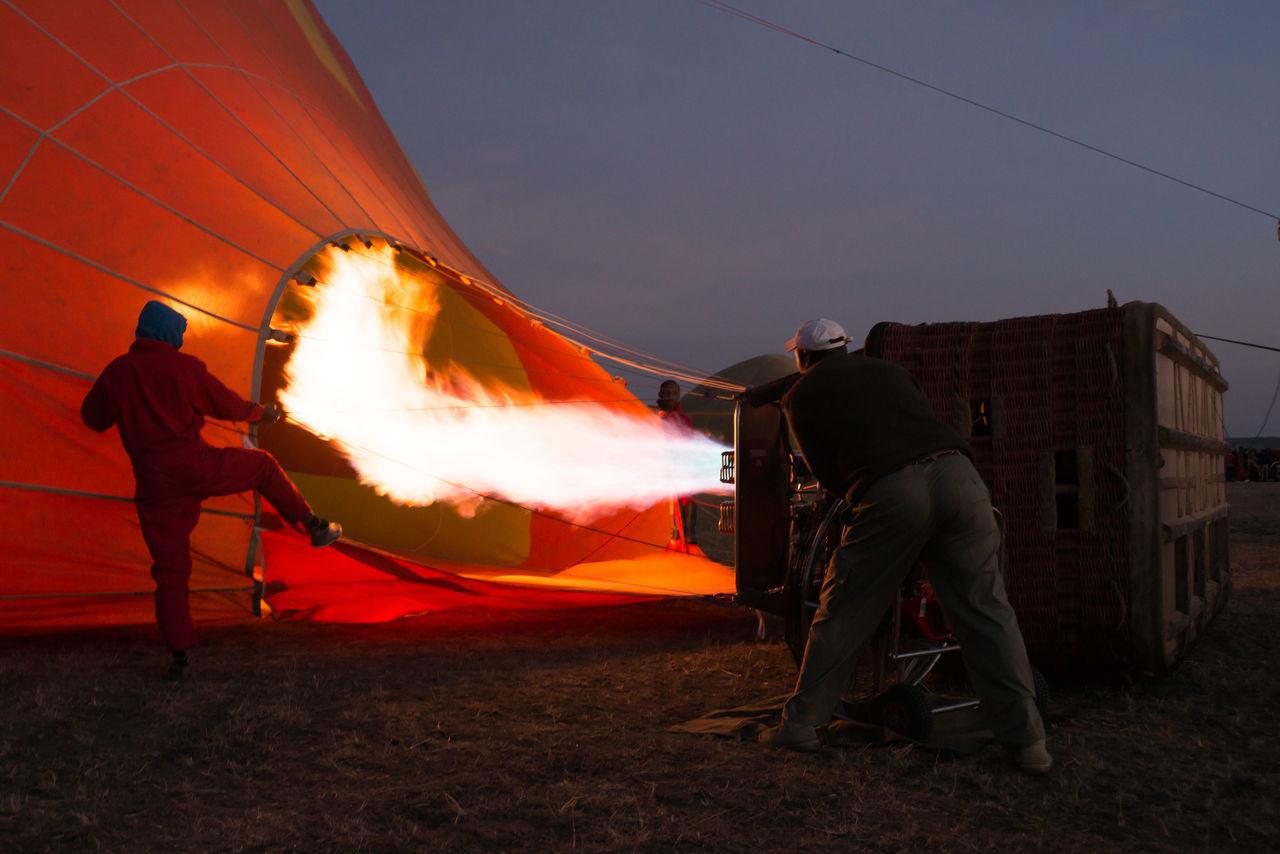 Men Prepping Hot Air Balloon On Field Against Sky