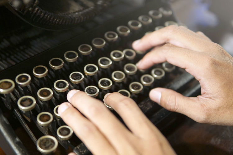 Cropped hands using typewriter at table