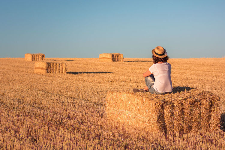 Rear view of woman sitting over hay bale on field against clear sky