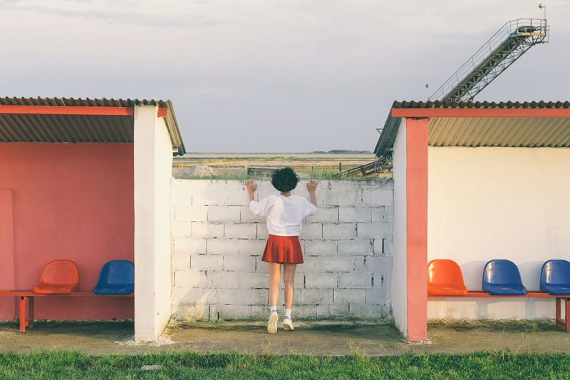 Rear view of girl standing against sky