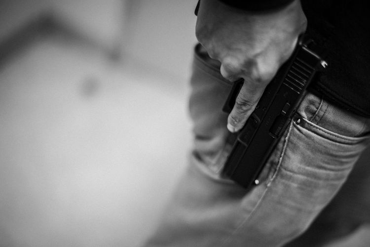 Midsection of man holding gun