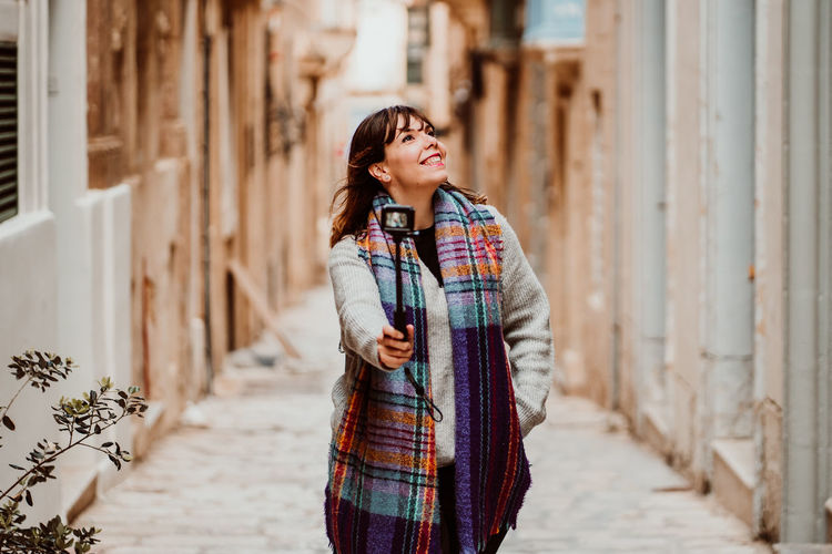 Happy woman looking away while standing outdoors