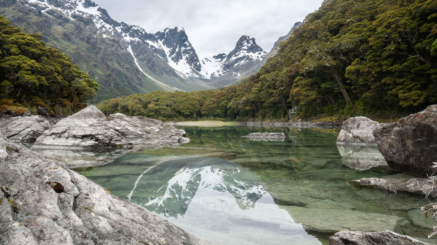 Pristine alpine lake reflecting surrounding environment. shot on routeburn track, new zealand