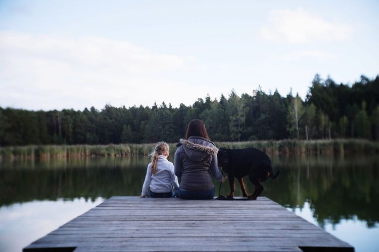 Rear view of mother sitting with daughter and dog on pier in lake