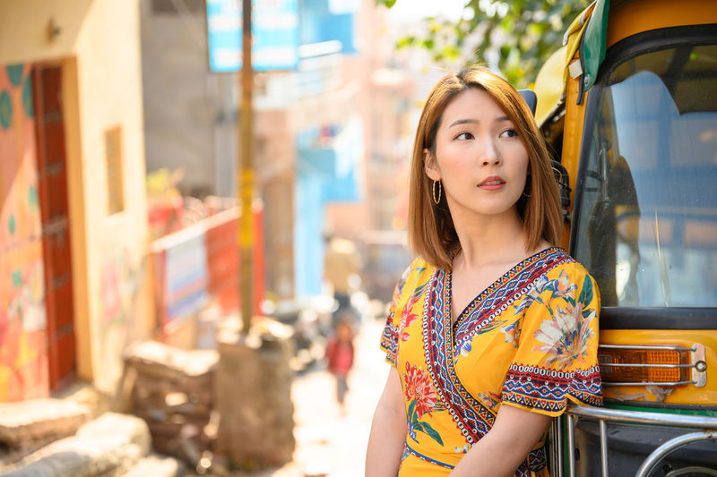 Beautiful woman looking away while standing by jinrikisha