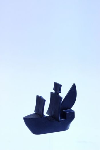 Close-up of shoes against clear blue sky