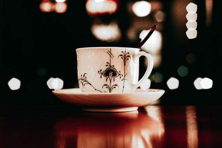 Porcelain Teacup On Table Against Defocused Background