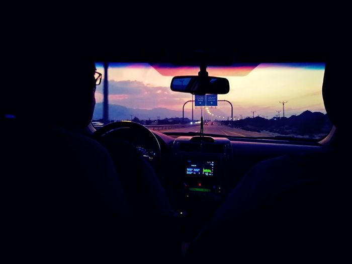 Rear view of silhouette man in car at sunset